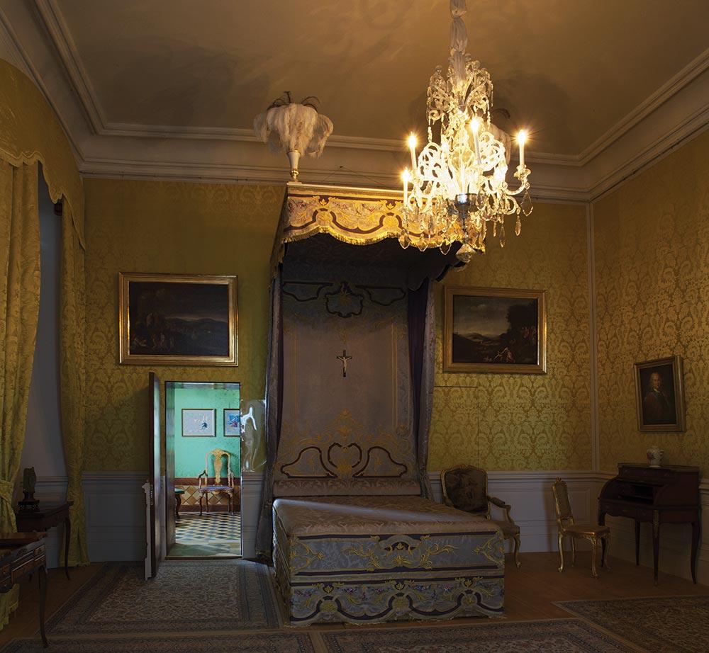 Hercogienes guļamistaba ar rekonstruēto gultu. Apgaismojums imitē sveču gaismas doto krēslas pakāpi.